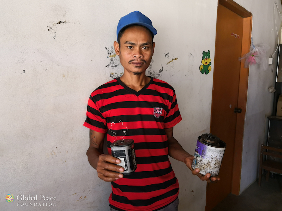 Villager holds 6v battery and kerosene used for fuel