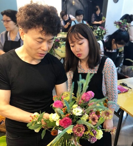 Myeon Oh shows student how to arrange flowers