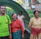 A Nepalese family stands next to a temporary shelter, helped built by Rise Nepal.