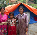Roshani (right) with her family in front of their makeshift tent.