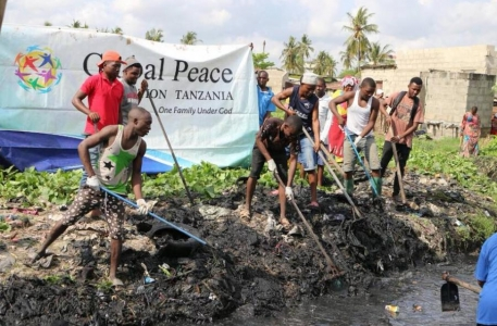 Global Peace Foundation - Tanzania Youth Environment Clean up Project - people raking debris from water