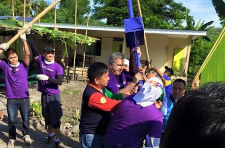 Volunteers and Rhicke Jennings, Managing Director of FedEx Philippines and Indonesia set up a solar street light for Global Peace Foundation's first All Lights Village in Tarlac, Philippines