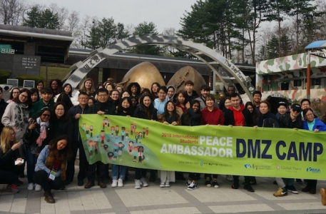 International Peace Ambassadors hold up their banner while Camping at Korea's Demilitarized Zone