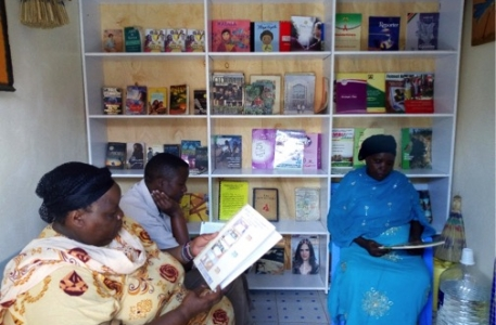 A group of adult women from Soweto-Embakasi sample books at the Global Peace Foundation - Women - Kenya library