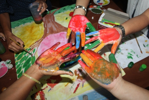 Workshop participants getting their hands dirty while working on their art poster.