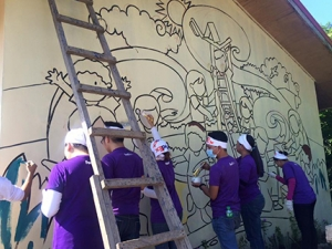 Global Peace Foundation volunteers paint mural on school building.